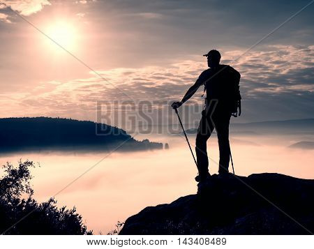 Tall Tourist With Poles In Hand. View Point Above Heavy Misty Valley.