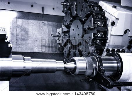 Rotating head with drilling machine bits and tools in high precision mechanics plant at CNC lathe in workshop
