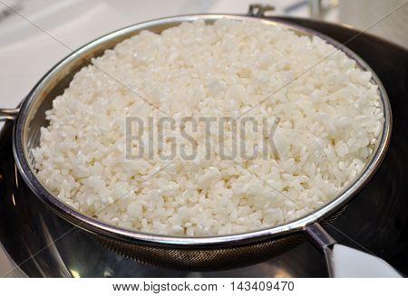 White raw rice lies in a colander