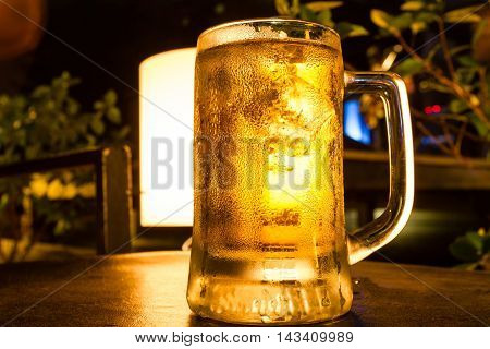 Glass of light beer on table for party