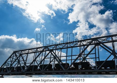 Steel railroad bridge over the river on sky background