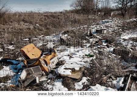 Old armchair on dump. Garbage and wastes. Stock image.