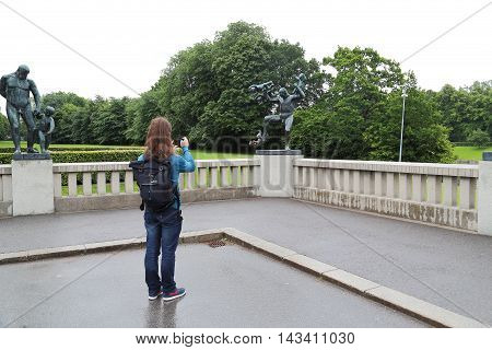 OSLO, NORWAY - JULY 1, 2016: Tourist takes pictures in the memory of sculptures of rhe bridge in the Vigeland Sculpture Park.