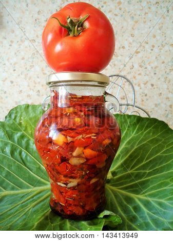 Fresh tomato on the a jar of sun dried tomatoes, garlic and rosemary