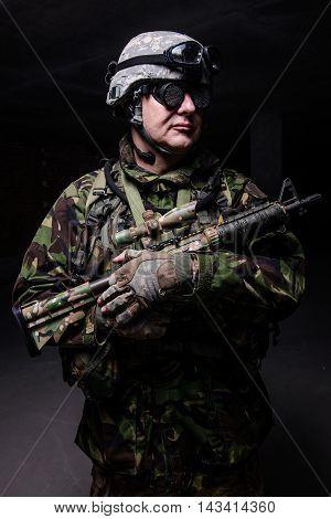 Man with gun in uniform helmet and strange glasses on dark background