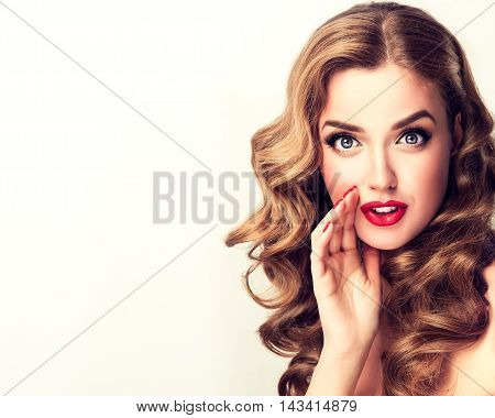 Beautiful girl with bright makeup and curly hair telling a secret .Portrait young happy woman model whispering about something. Expressive facial expressions