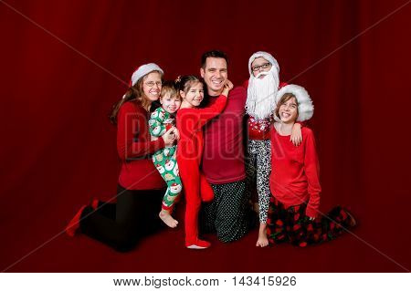 A family dressed in Christmas colors and some Santa Claus apparel poses for a Christmas portrait on red.
