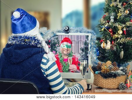 Back view of woman in blue hat with white pigtails sits at the desk and drinks sparkling wine with mature man in Santa Claus costume, green domino eye mask in monitor. This couple of friends wish a Merry Christmas each other during online video chat