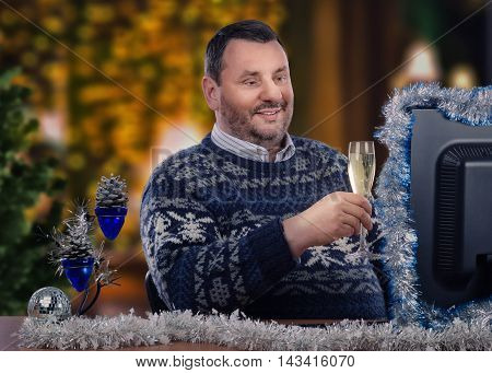Mature man proposes Christmas toast with glass of white wine during online video chat. Bearded man in Scandinavian sweater sits at the desk with tinsel garlands. He looks at the monitor his face illuminated by the screen light