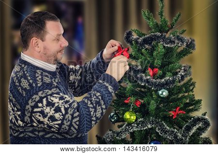 Standing sideways mature man hangs red bow on Christmas tree with pleasure. Bearded man wears Scandinavian sweater. Half body portrait. Horizontal shot on blurry indoors background