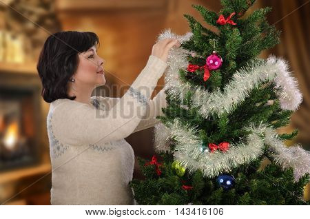 Mature woman decorating Christmas tree with white-silver tinsel garland. Standing sideways black-haired woman wears Norwegian blue and white sweater. Half body portrait. Horizontal shot on blurry indoors background