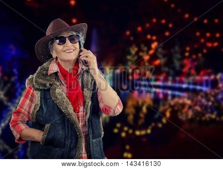 Cheerful senior cowgirl in sleeveless sheepskin jacket calls on mobile phone. Old stunning woman in sunglasses wears brown cowboy hat, red plaid shirt, red neckerchief is posing on outdoors Christmas blurry decoration background