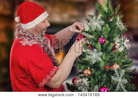 Standing sideways mature bearded man in Santa Claus costume hangs red ball on Christmas tree. Half body portrait. Horizontal shot on blurry indoors background