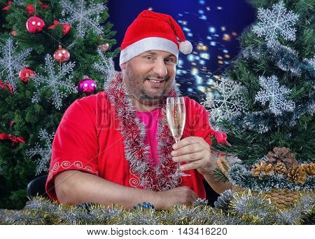 Smiling mature fat man in Santa Claus costume holds glass of white wine by left hand. Bearded man sits at the desk surrounded decorated Christmas trees, tinsel garlands, balls, snowflakes. He looks at camera