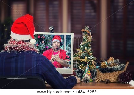 Back view of young man in dark navy plaid shirt, red hat sits at the desk and looks at clapping Santa Claus singing Ho Ho Ho I wish you a Merry Christmas in monitor. There are small decorated Christmas tree, basket pine cones on wooden desk