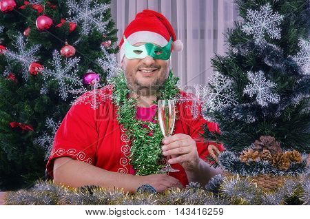 Chubby faced mature smiling man in Santa Claus costume toasting glass of white wine. Bearded fat man in green domino eye mask sits at the desk surrounded decorated Christmas trees, tinsel garlands, balls, snowflakes, pine cones. He looks at camera