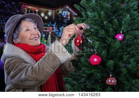Stunning old woman in beige sheepskin coat hangs on Christmas tree a red ball. Standing sideways senior woman in red knitted scarf, soft cashmere wool hat decorating Christmas tree with pleasure. Half body portrait