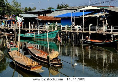 Samut Songkhram Thailand - December 29 2011: Old wooden fishing boats docked in front of a cluster of Thai houses at a small fishing village nestled on the banks of an estuary