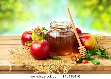 Honey apple and pomegranate on wooden table over bokeh background