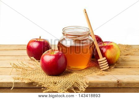 Honey and apples on wooden table over white background
