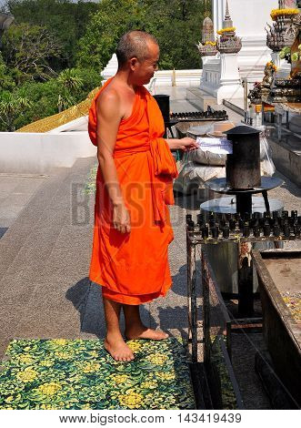 Saraburi Thailand - January 8 2013: Barefoot Buddhuist monk wearing an orange robe burning ceremonial paper at Wat Phutthabat shrine