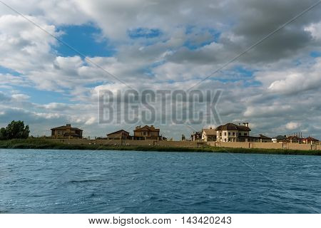 Summer beautiful landscape with river, blue sky, clouds and elite cottage area