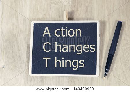 sentence Action Changes Things written with chalkboard with pen and wooden desk
