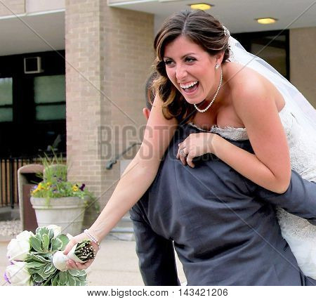 A bride gets carried away by the groom on his shoulder