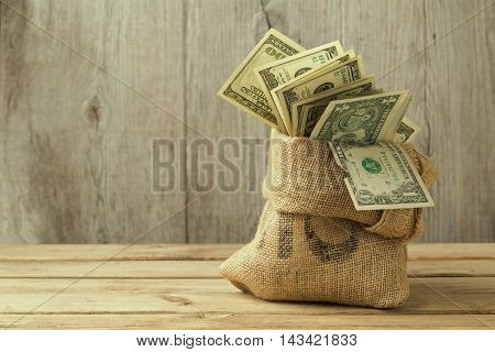 Money in sack on wooden table, saving concept