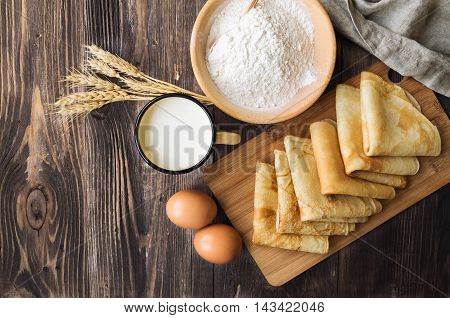 Fresh homemade crepes with ingredients and ears of wheat on rustic wooden background. Top view.
