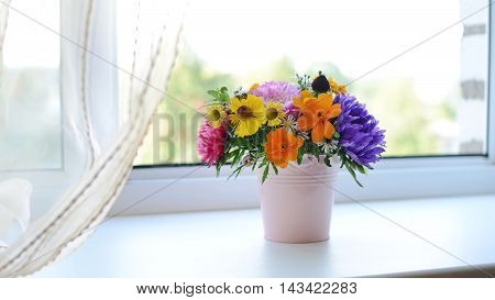 Multi-colored bouquet of different autumn flowers in the pot on the windowsill