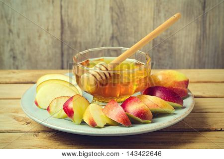 Honey and sliced apple on plate over wooden background for Jewish New Year Rosh Hashahah