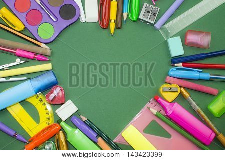 Different colorful school supplies in heart shape on green background.