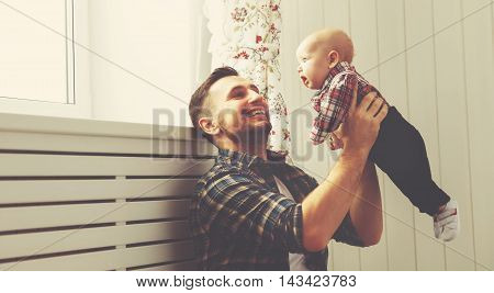 Happy family father and child baby son playing together at home