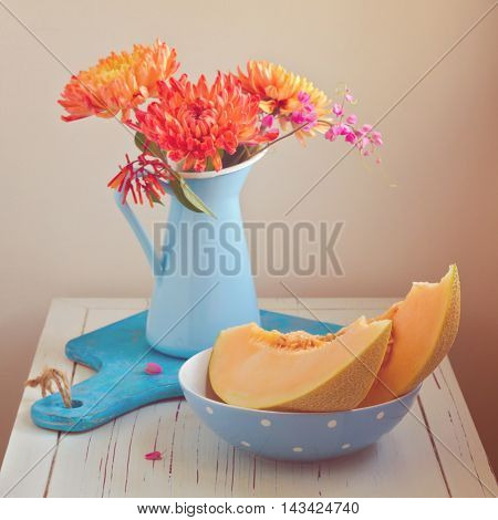 Melon and flowers on vintage table. Focus on melon. Retro filter effect