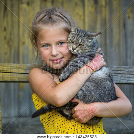 Funny little girl holding a cat in her arms.