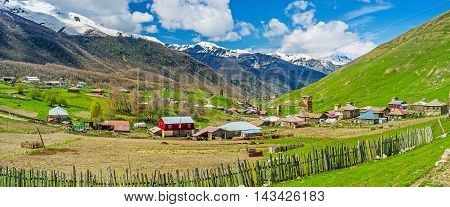 The old wooden fence and kitchen garden with old houses and Svan towers on the distance in Zhibiani village of Ushguli comunity Georgia.