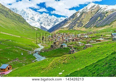 The amazing view of Zhibiani village next to the winding Enguri river and snowy Shkhara Mount on the background Ushguli Georgia.