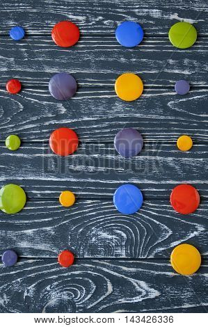 A Set Of Colorful Glass Buttons For Clothes On A Dark Wooden Background.