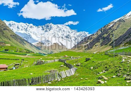 The unique nature of Caucasus mountains with bright green slopes located adjacent to the cold and snowy peaks Ushguli Upper Svaneti Georgia.