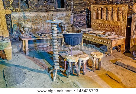 USHGULI GEORGIA - MAY 22 2016: The carved wooden benches and chairs stands around the cauldron for cooking over an open fire in Ethnographic Museum in the medieval house of Svan family on May 22 in Ushguli.