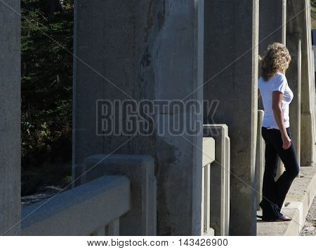 Sexy blonde haired woman standing on a bridge