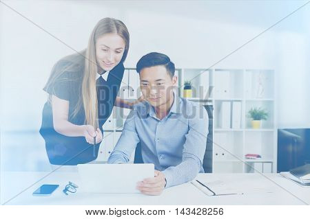 Man holding tablet. Woman pointing at screen with pencil and smiling. Concept of office work. Toned image