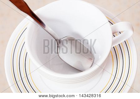 Teacup And Saucer With A Spoon On A White Background