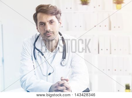 Portrait of general practice doctor sitting in his office and looking at viewer attentively. Concept of illness and cure. Toned image