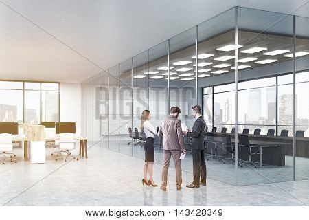 Team of colleagues are standing in hall near conference room with glass walls and discuss work issues. Concept of teamwork. 3d rendering mock up toned image