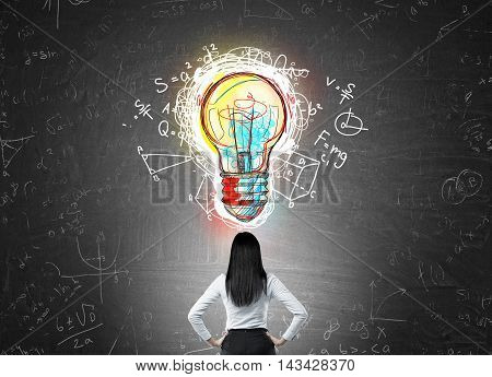 Woman with black hair in suit standing with back to camera looking at light bulb sketch on chalk board. Concept of science discovery