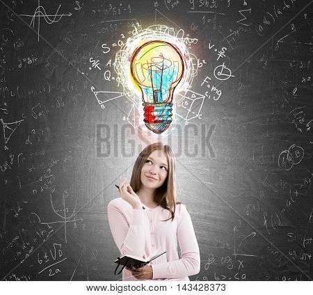 Woman standing near blackboard with colorful light bulb sketch and formulas. Concept of exact sciences.