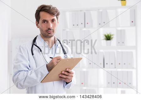 Doctor with clipboard taking notes and looking to camera while standing in his office. Concept of attentive specialist