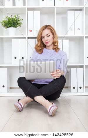 Serious woman sitting on office floor with her large white tablet and legs crossed. Concept of doing job well
